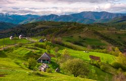 Mountainous rural area in springtime. Agricultural fields and orchards on a grassy slopes.  outdated industrial approach, traditional farming concept Royalty Free Stock Photos
