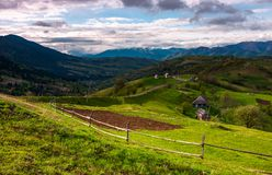 Mountainous rural area in springtime. Agricultural fields and orchards on a grassy slopes.  outdated industrial approach, traditional farming concept Stock Photos