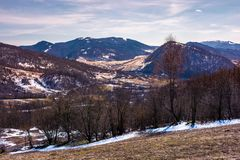 Mountainous scenery of Uzhansky National Park. Leafless forest on hills with weathered grass and some snow in springtime Royalty Free Stock Photography