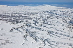 Mountainous terrain, ravines, erosion of the surface around the. Volcano on the Kamchatka Peninsula. Neighborhood Karymsky volcano after a fresh snowfall in the Royalty Free Stock Photo