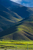 Mountainous Tibetan landscape. Scenic view of mountainous Tibetan landscape with green fields in foreground Stock Image