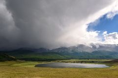 Mountains湖阴云密布暴风云阳光 免版税图库摄影