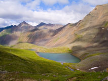 Mountains. Mountain lake, high mountains, landscape, cloudy sky, turquoise water, green grass, beautiful scene, destination of travel, Sayan royalty free stock image