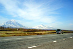 Mountains. Car goes on road on background of the snow-clad mountains Stock Image