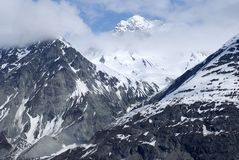Mountains in Alaska. Glorious mountains covered by clouds and snow in Glacier Bay national park, Alaska Stock Photography