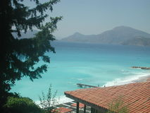Mountains Along a Beautiful Coastline. Beautiful blue water of the Mediterranean Sea meet the sandy beach and mountainous coastline near Fethiye, Turkey royalty free stock photo