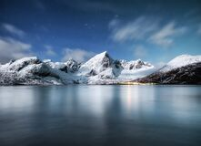 Free Mountains And Reflections On Water At Night. Winter Landscape. The Sky With Stars And Clouds In Motion. Nature As A Background. Royalty Free Stock Photos - 175024438