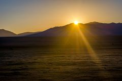Song Kul lake with horses in sunrise. Mountains around Song Kul lake and horses in a sunrise sun, Kyrgyzstan Stock Photo