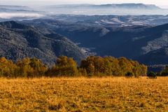 Mountains autumn landscape. Nature season specific landscape: mountain area by autumn with descents covered by dry yellow grass and aerial view on mountains far Stock Photo