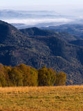 Mountains autumn landscape. Nature season specific landscape: mountain area by autumn with descents covered by dry yellow grass and aerial view on mountains far Stock Photography