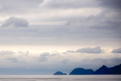 Mountains from the Bay of Alaska. Cloudy evening skies over the Bay of Alaska. Distant mountains over calm, cold waters Royalty Free Stock Photo
