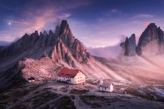 Mountains with beautiful house and church at sunset in autumn