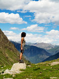 Mountains beauty. A girl on a big stone contemplating a summer mountain landscape. This picture is from Alps, in Italy royalty free stock photos