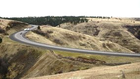 Cars and trucks make the curve climbing steep incline Oregon Highway. The mountains begin here in Oregon on the divided highway stock video