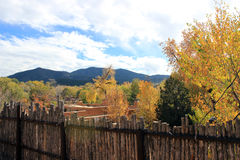 Mountains behind the Fence. A wooden fence precedes the autumn woods with mountains in the background Stock Photo
