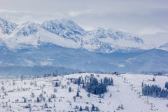 Mountains behind ski resort Stock Images