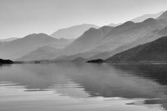 Mountains in a black&white with reflections on a water. Black&white photograph of the lake Skadar and mountains around it in Montenegro on a sunny day Stock Images