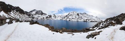 Mountains blue lake, Gosaikunda ridge peaks panorama. Mountains frozen blue lake panorama, snow covered peaks. Gosaikunda trekking route, Langtang mountains stock photography