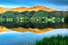 Mountain Landscape with A Village, Green Forest and Blue Sky Reflected in Lake in Summer royalty free stock photo