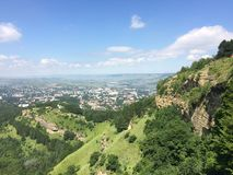 Mountains of the Caucasus. On a sunny summer day. beautiful view from the top of a cliff on a blue sky with clouds and a green forest Stock Photos
