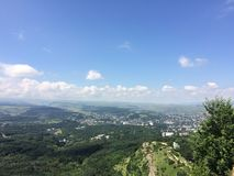 Mountains of the Caucasus. On a sunny summer day. beautiful view from the top of a cliff on a blue sky with clouds and a green forest Stock Images