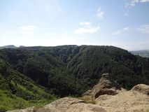 Mountains of the Caucasus. On a sunny summer day. beautiful view from the top of a cliff on a blue sky with clouds and a green forest Royalty Free Stock Images