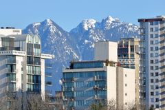 Mountains and City Architecture. Hi rise, high density towers stand in front of snow capped mountains stock image