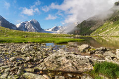 Mountains clean lake among stones. Shallow mountains clean lake among moss stones with snow capes on the background stock photo