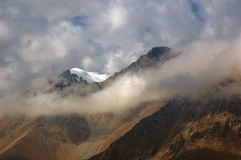 Mountains in clouds. Sunlited mountains in the clouds Stock Photo
