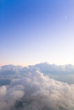 Mountains of Clouds. Image has a vertical orientation. Small crescent moon hovers above soft clouds in the sky. Image photographed from an airplane at 30,000 Royalty Free Stock Images