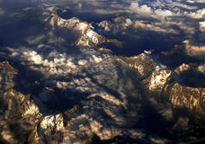 Mountains and clouds. An airplane view of mountains and clouds between Italy and France during sunset Stock Photos