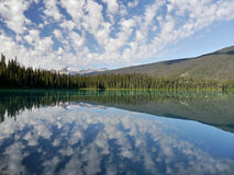 Mountains and clouds reflected in a mountain colored lake. Royalty Free Stock Photo