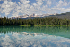 Mountains and clouds reflected in a mountain colored lake. Stock Photos