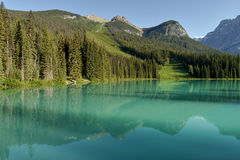 Mountains and clouds reflected in a mountain colored lake. Stock Image