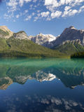 Mountains and clouds reflected in a mountain colored lake. Royalty Free Stock Photography