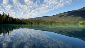 Mountains and clouds reflected in a mountain colored lake. Royalty Free Stock Images
