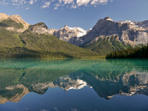 Mountains and clouds reflected in a mountain lake. Royalty Free Stock Images