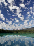 Mountains and clouds reflected in a mountain lake. Stock Photos