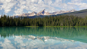 Mountains and clouds reflected in a mountain lake. Royalty Free Stock Photo