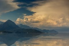 Mountains and clouds are reflected in the sea water. City Of Kemer, Turkey. Beautiful sunrise city of Kemer, Turkey. Mountains and clouds are reflected in the Stock Photos