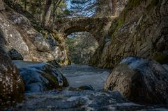 Romanesque bridge over turbulent waters. Rio Lozoya. Through the mountains of the community of Madrid it is common to find currents of water that meander between stock photo