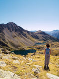 Mountains contemplation. A girl staring at the beautiful mountain landscape with a lake, grass and snow. This picture is from Alps, in France. The lakes are Royalty Free Stock Photos