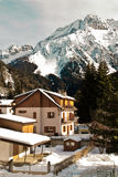 Mountains Country House. House in mountain landscape during winter on the foreground, mountain peak on the background.Apartments in Ponte di Legno, Italy royalty free stock images