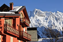 Mountains Country House. House in mountain landscape during winter on the foreground, mountain peak on the background. Apartments in Ponte di Legno, Italy stock photos