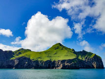 Mountains covered in green with water and sky Stock Photo