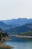 Mountains covered by pine forests descending to lake Stock Photos