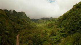 Mountains covered with rainforest, Philippines, Camiguin. Mountains covered rainforest, trees and river in cloudy weather, aerial drone. Camiguin, Philippines royalty free stock images