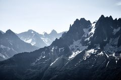 Mountains and snow peaks of France. Mountains covered by snow and ice with dark rocks royalty free stock images