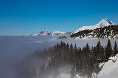 Mountains covered with snow and surrounded by clouds Stock Photography