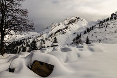 Mountains covered with snow and surrounded by clouds Stock Images